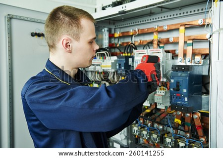 electrician inspector cheching power of fuseboard equipment in boiler room - stock photo