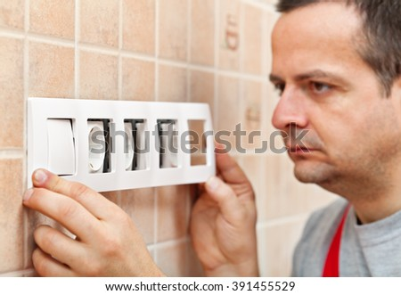 Electrician installing a decorative panel on electrical wall fixture - closeup, focus on frame - stock photo