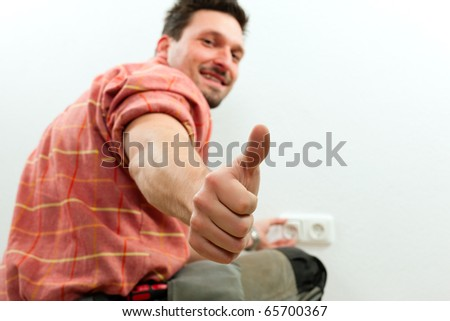 Electrician installing a power socket giving the thumbs-up sign - focus on thumb - stock photo