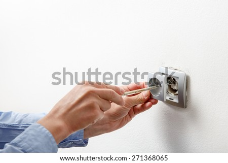 Electrician installing a silver wall-mounted AC power socket with a screwdriver on a white wall, renovating home.