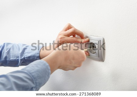 Electrician installing a silver wall-mounted AC power socket with a screwdriver on a white wall, renovating home.  - stock photo