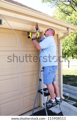 Electrician installing electric cable to update outside lighting for better security - stock photo
