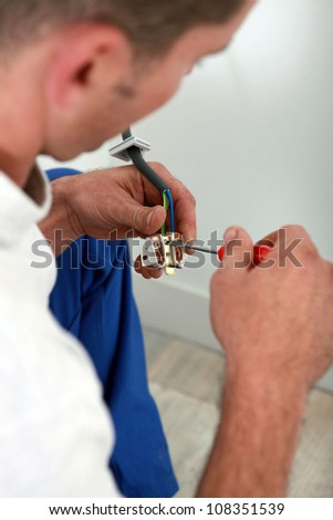 Electrician installing electrical outlet - stock photo