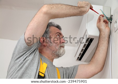 Electrician installing electrical plug for air conditioner - stock photo