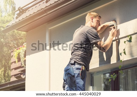 electrician installing lamp on house facade - stock photo