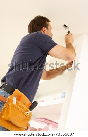 Electrician Installing Light Fitting In Home - stock photo