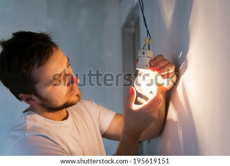 Electrician installing light in a new house - stock photo