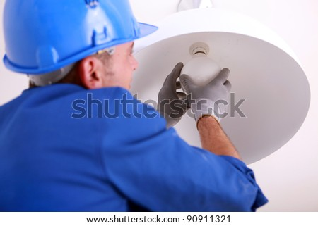 Electrician installing new light bulb - stock photo