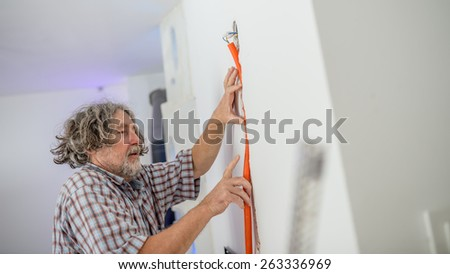 Electrician installing recessed wiring in a wall fitting the conduit into the groove , low angle view in a house renovation concept.