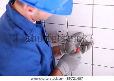 Electrician installing switch on wall