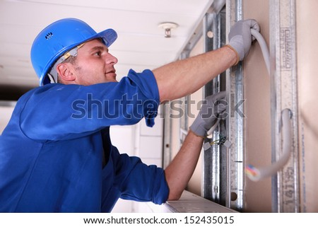 Electrician installing wiring - stock photo