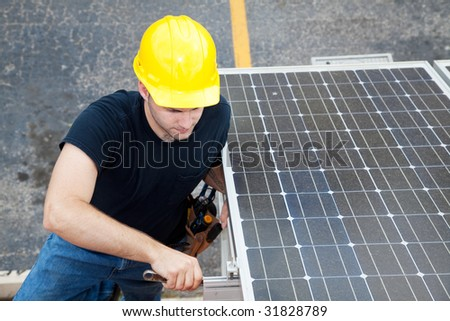 Electrician installs solar panels on the side of a building. - stock photo