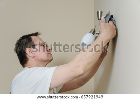 Electrician is instilling a wall lamp with led bulb.