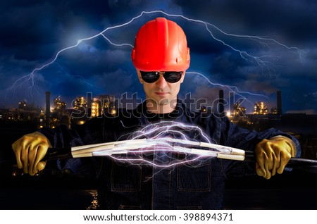 Electrician keeps cables that shoot lightning on the background of industrial landscape and sky with lightning
