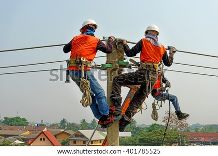 Electrician lineman repairman worker at climbing work on electric post power pole, Thai language same safty fist in English language