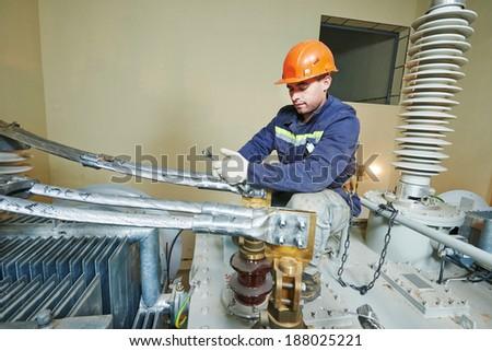 Electrician lineman repairman worker at huge power industrial transformer installation work - stock photo