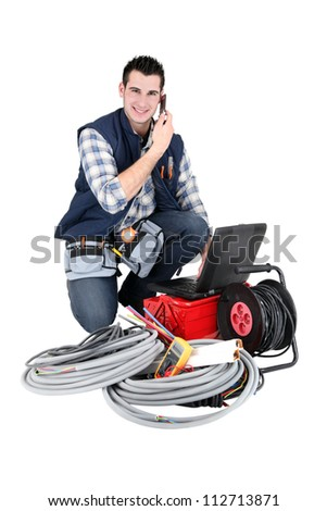 Electrician making a call whilst kneeling by his equipment - stock photo