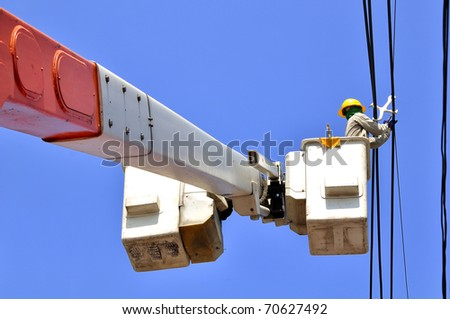 Electrician Man on electric poles. Electrical repairs are made to restore them to normal. - stock photo