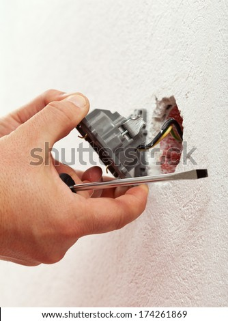 Electrician mounting electrical wall fixture - closeup on hands