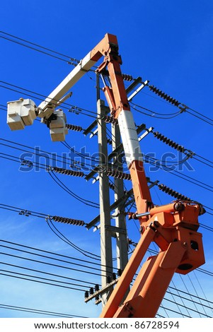 Electrician on crane and  repairs a wire of the power line - stock photo