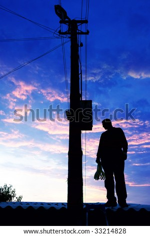 Electrician on the roof looking around before repairs power line - stock photo
