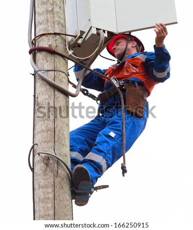 Electrician opened the control panel on the pole reclosers with the use of claws-manholes and belt