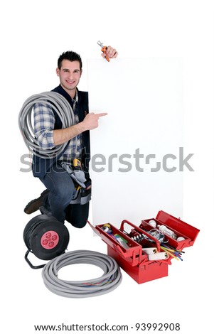 Electrician pointing a white sign for message - stock photo