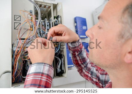 Electrician repairing a fusebox - stock photo