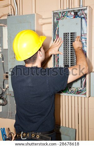 Electrician repairing circuit breakers in industrial electric panel. - stock photo