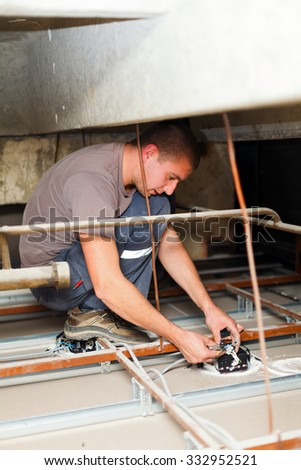 Electrician repairing electric devices using utensils and cables. - stock photo