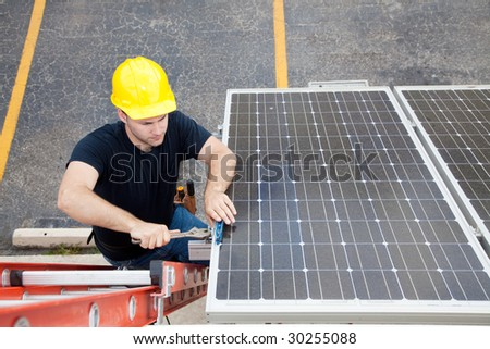 Electrician repairing solar panel.  Wide angle view with room for text. - stock photo