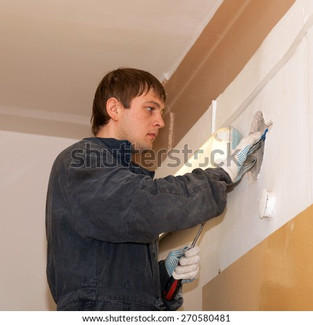 Electrician repairing wiring hidden in the wall of a building under plaster  - stock photo