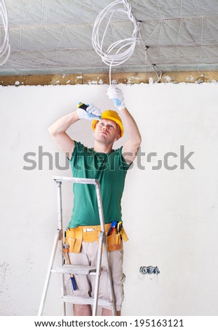 electrician stand on ladder with knife - stock photo