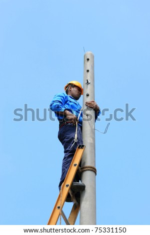 Electrician stays on the tower electric pole and repair the power line - stock photo