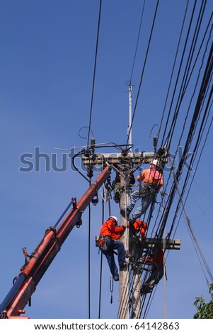 Electrician stays on the tower pole and repairs a wire of the power line - stock photo