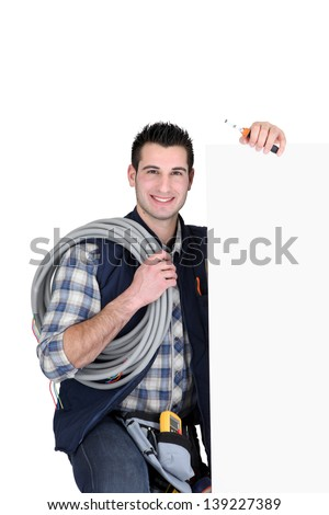 Electrician stood by poster - stock photo