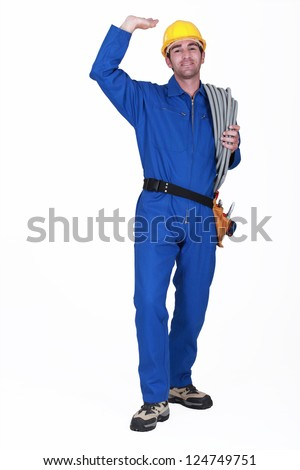 Electrician stood with coil of electrical wiring - stock photo