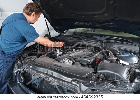 Electrician testing car electronics with multimeter at garage. Repairman working with automobile inside with electrical tester in his hands. - stock photo