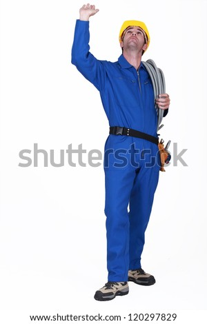 Electrician touching ceiling - stock photo