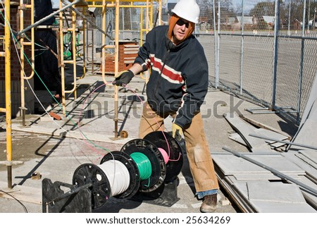 Electrician Unwinding Wire - stock photo