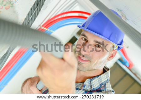 Electrician wiring a ceiling - stock photo
