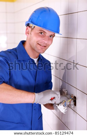 Electrician wiring a large tiled room