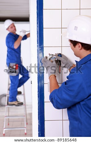 Electrician wiring a wall socket