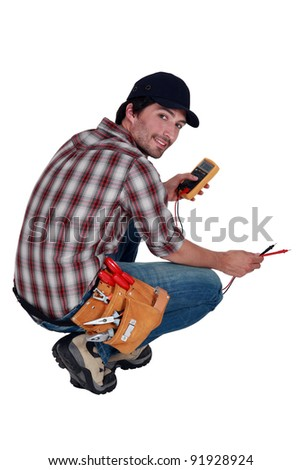 Electrician with a multimeter - stock photo