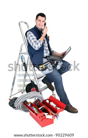 Electrician with a phone and laptop - stock photo