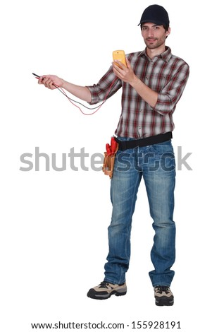 Electrician with a voltmeter - stock photo