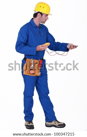 Electrician with an multi-meter - stock photo