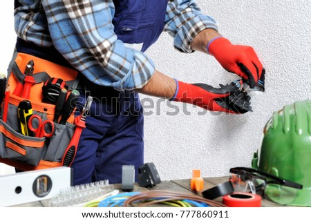 Electrician With Hands Protected By Gloves And Insulated Tools Works Respecting The Safety Regulations In A