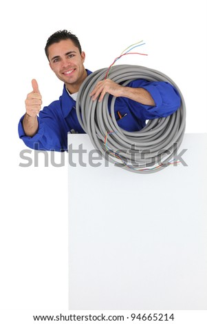 Electrician with long cable giving the thumbs-up - stock photo