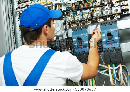 electrician worker checking voltage of the electric power switch in fuse board - stock photo